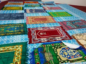 Variety prayer mats on the floor.